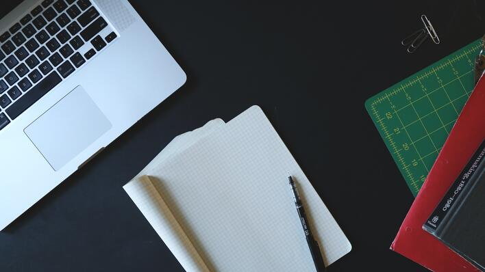 Detail of an open laptop and notebook, plus a pen