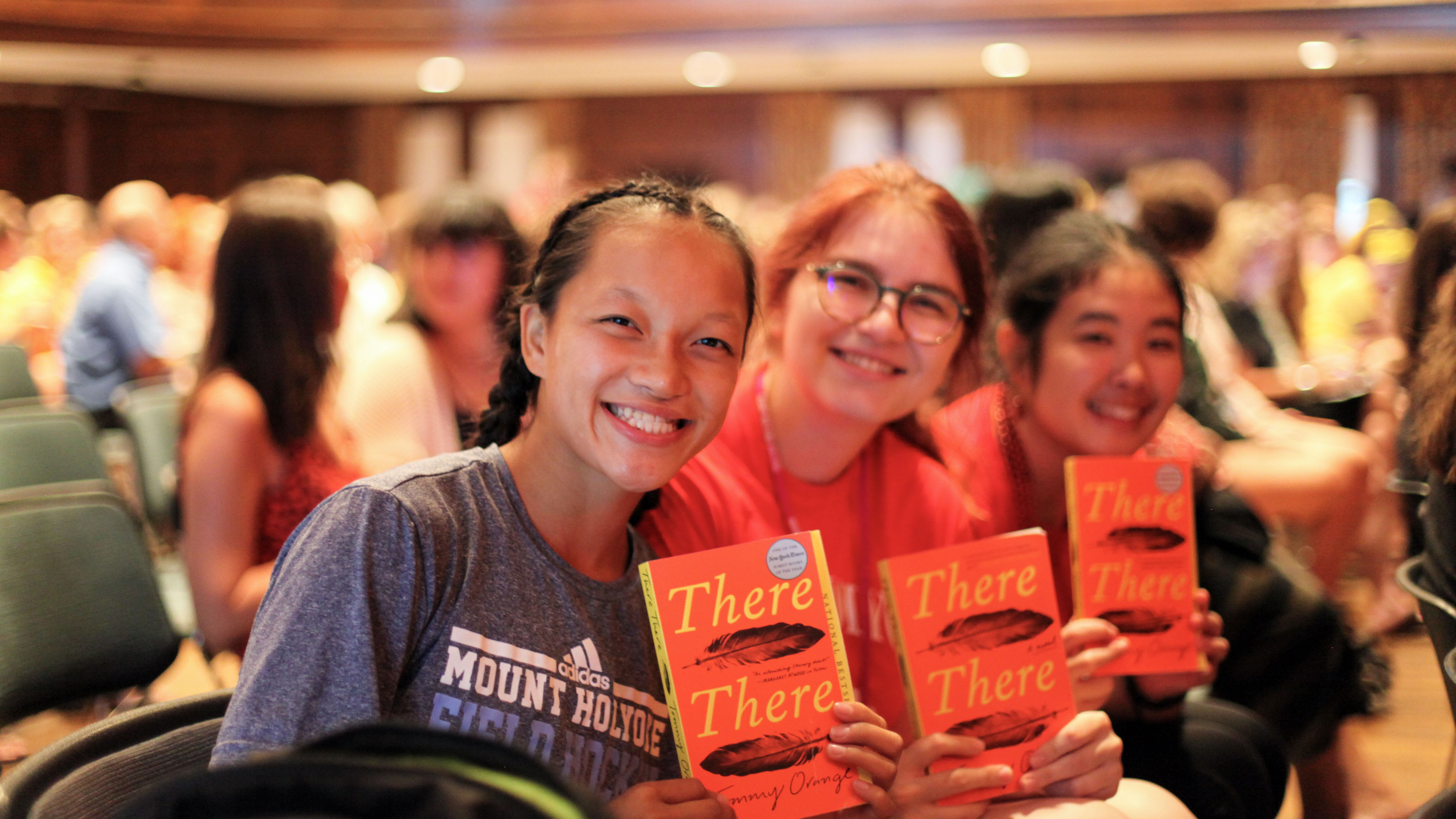 """Audience members holding copies of Tommy Orange's novel """"There There"""""""