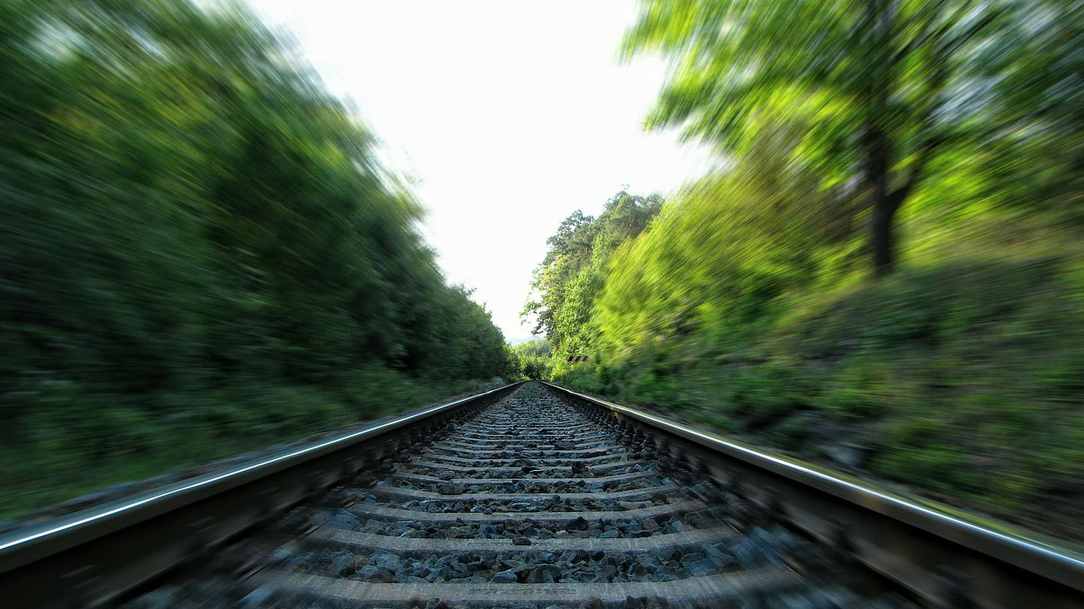 close up of train tracks and the blur of passing trees