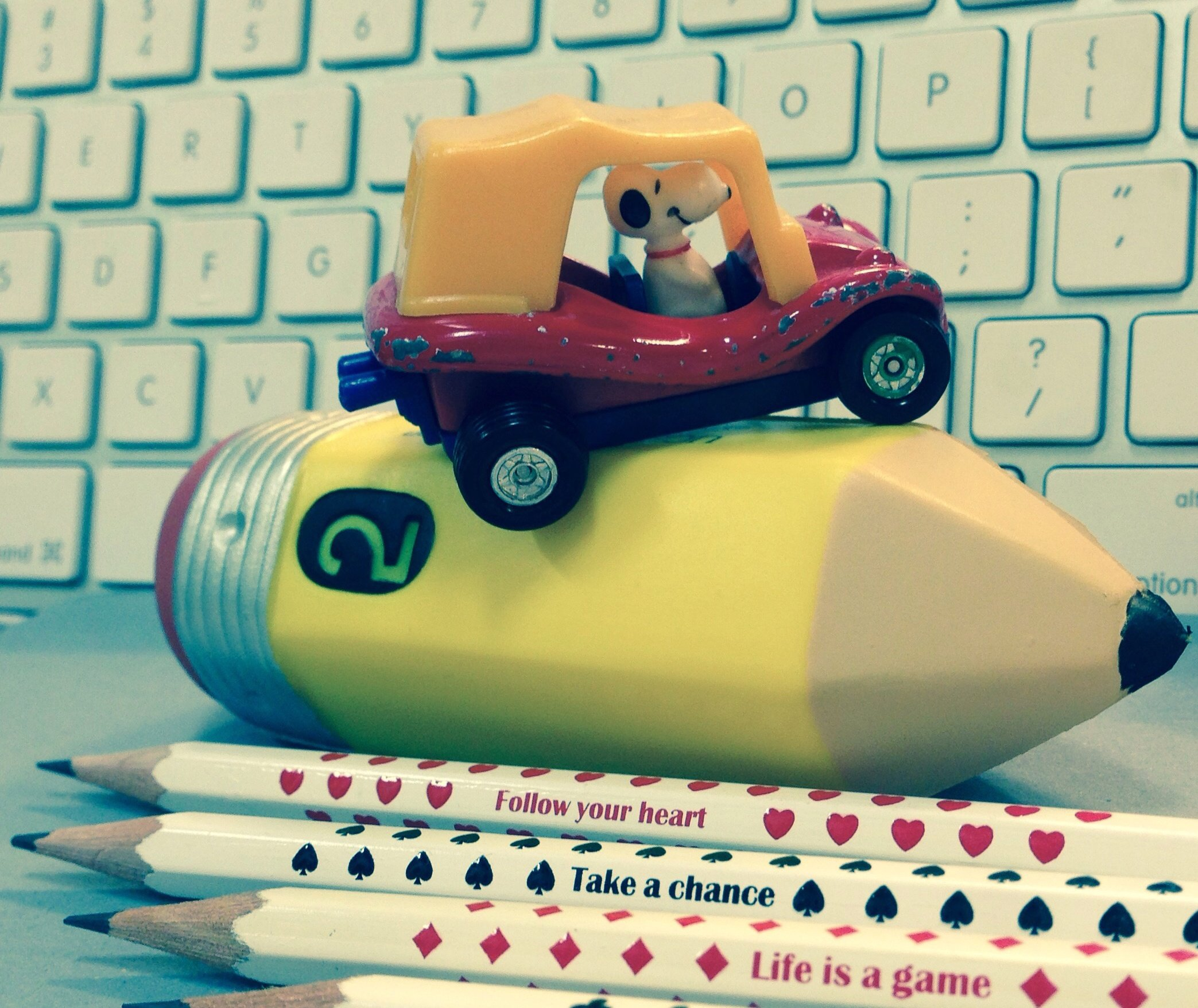 Vintage snoopy in metal toy car atop a large toy pencil