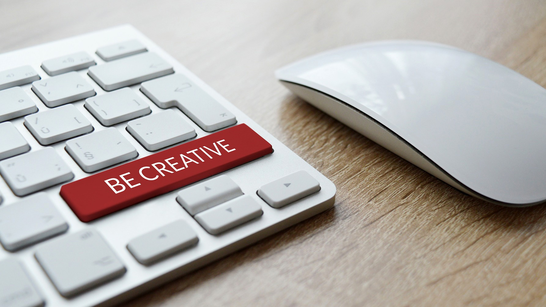 "A closeup of a keyboard featuring a red ""Be Creative"" button"