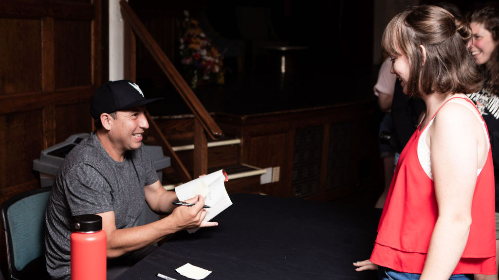 """Tommy Orange (left) signs a student's copy of """"There There"""""""