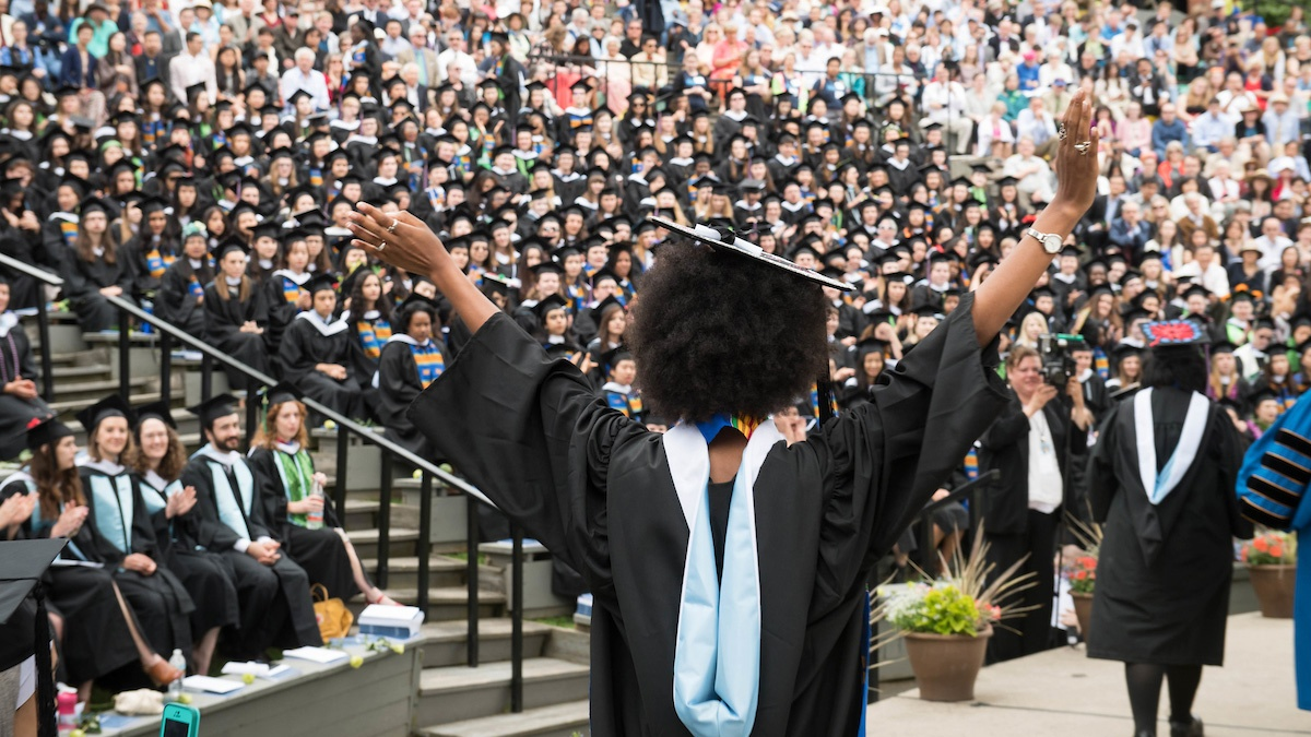 A student strikes a power pose, Commencement 2017