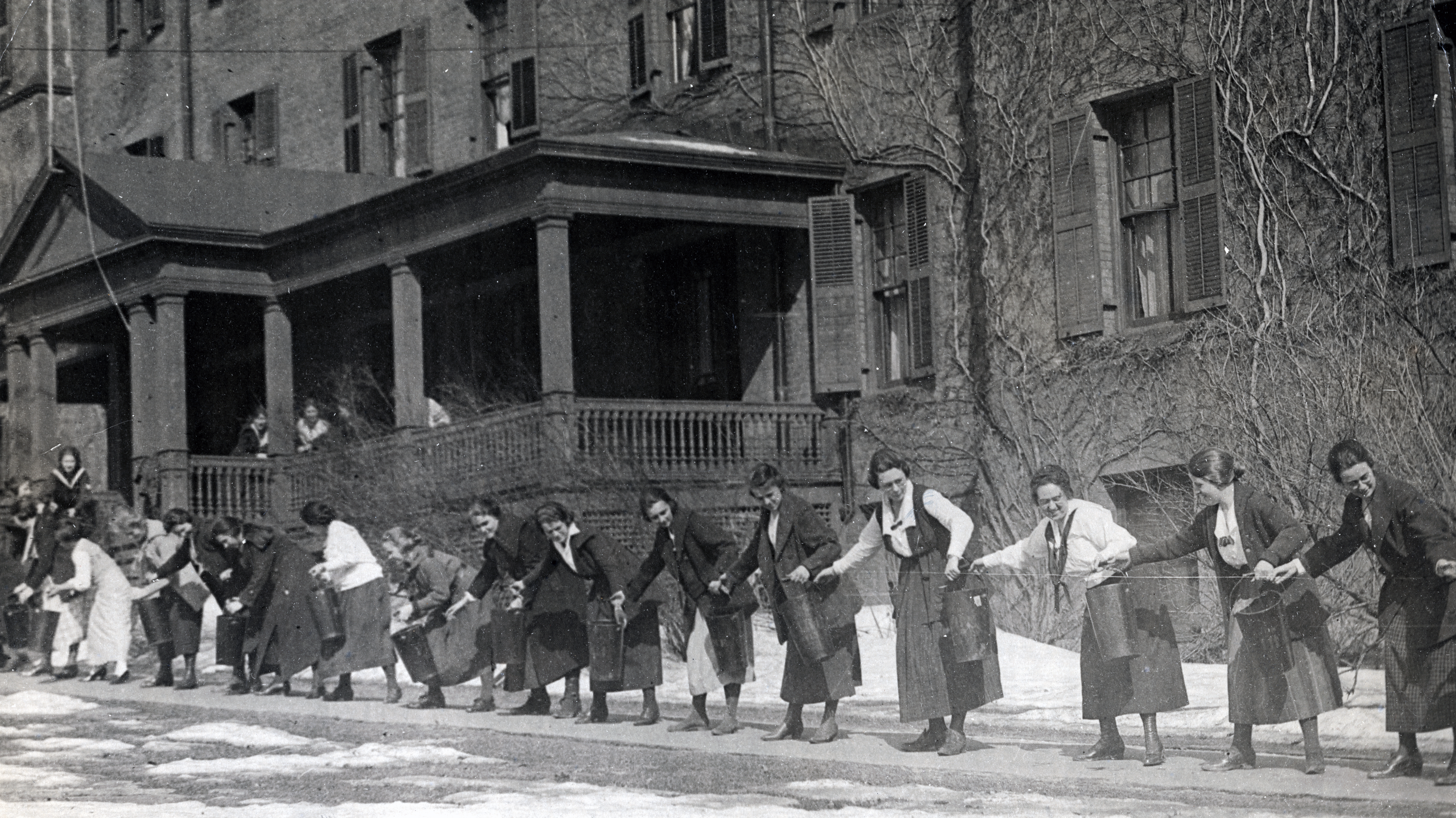 Students pass buckets full of water up a rope during fire drill, October 1920