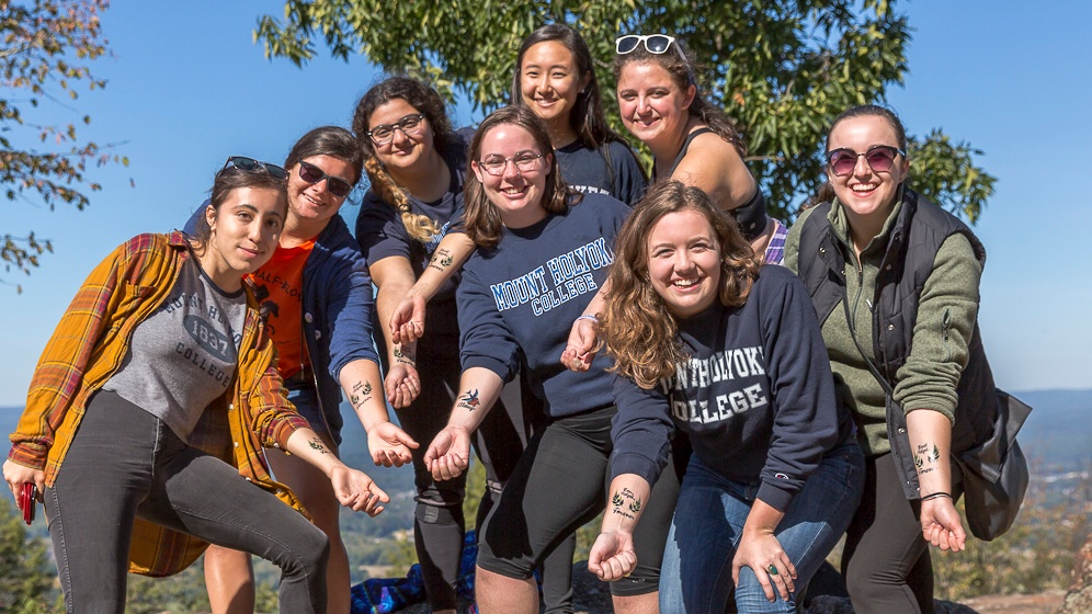 Photo of a group of students showing off their Mount Holyoke Forever tattoos